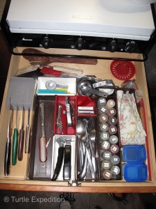 """Organization and maximum use of space is critical in a small camper. 35mm film cans held spices that can be refilled as needed from the """"pantry""""."""