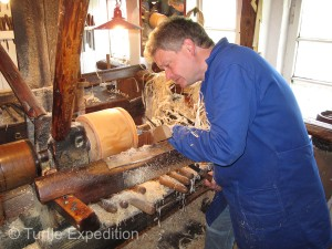 "Using memory and feel, master craftsmen shape ""hoops"" from the carefully chosen tree trunks on a lathe."