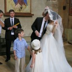 """""""You may kiss the bride"""". The flower girl and the ring bearer seemed fascinated."""