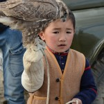 A young future eagle hunter holds a small hawk. The eagle hunting tradition is passed from one generation to another.