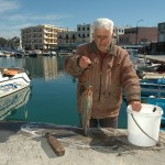 We watched an old fisherman mercilessly beating an octopus on the pier to tenderize it.