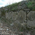 Old rock walls had been built, rebuilt and built again using whatever material was available. Used grinding stones served their second purpose in life.