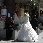 A Western style wedding dress was contrasted by the woman to the left with the headscarf while she texted on her cell phone.
