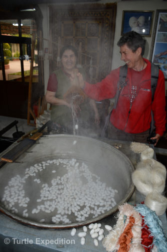 Monika is trying her hand on the art of unraveling silk cocoons. The water is very hot.