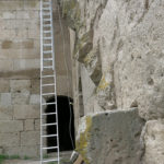 A ladder replaces the old stone steps set into the side of the wall.