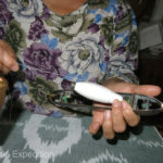 The lady inserts a bobbin into a boat shuttle she'll use for the weft on her loom.