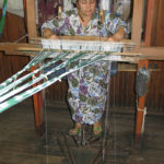 This lady is setting up her loom. The warp strands are still tied together.