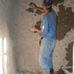 The father was adding mud to the walls of his new building.
