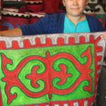 Dinara, the manager of the Altyn Kol handicraft shop, a women's co-operative, proudly displays a Shirdak (felt carpet) with a traditional design.
