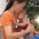 A young mother comforts her child, and you may notice there is no diaper. It's the Chinese way.