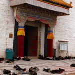 Monks gathered for prayer in one of the main temples leaving their shoes outside.