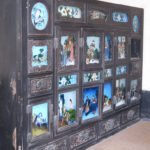 An antique closet was decorated with many paintings.