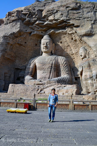 Green is standing in front of the largest outdoor Buddha at the Yungang Grottoes.