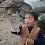 Not being an ornithologist, I could not tell if this was a hawk or maybe a young eagle being trained by this young boy for a future hunting career.