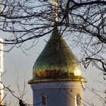 A golden onion tower of a Russian Orthodox church glows in the afternoon light.