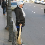 A lady picked up trash on a sidewalk using the typical Russian broom.