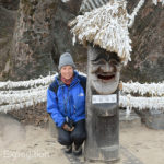 Monika poses with a carved figure in front of the 600-year old Zelkova Tree where the Goddess Samsin resides.