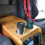A custom walnut center console holds maps, flashlights, auxiliary locks and all small travel accessories. It incorporates cup holders specifically sized for our Aladdin travel cups.