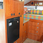 Next to the entry door is the refrigerator and cabinets purposely positioned over the wheel well.